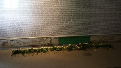 Wand der Namen in der KZ-Gedenkstätte Melk mit weißen Rosen.