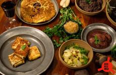 Ein Tisch gedeckt mit mittelalterlichem Essen.